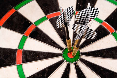 flew: Three darts in the bullseye. Checkered fletchings in focus. Stock Photo