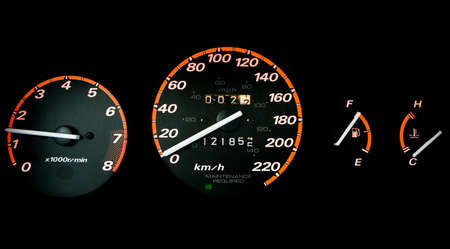 kilometre: Glowing car dashboard set against black background: tachometer, speedometer, tripometer, fuel and temperature guage.