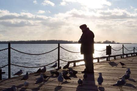 glint: Un anciano, silhouetted por el sol que brilla fuera del lago Ontario, alimenta las aves marinas por los muelles.
