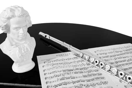beethoven: A flute, musical score and bust of Beethoven rest on a black piano top, isolated against a white background. Black and white (grayscale). Stock Photo