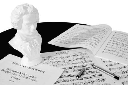 musicality: A bust of Beethoven, three scores and a fountain pen atop a black piano, isolated against a white background. Black and white (grayscale).