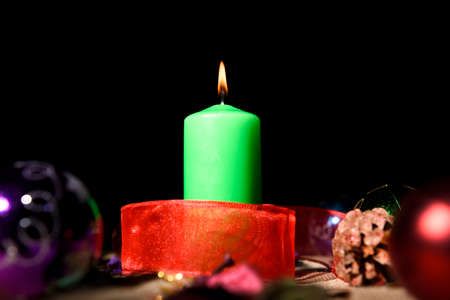 Green candle with red ribbon around it on black background.
