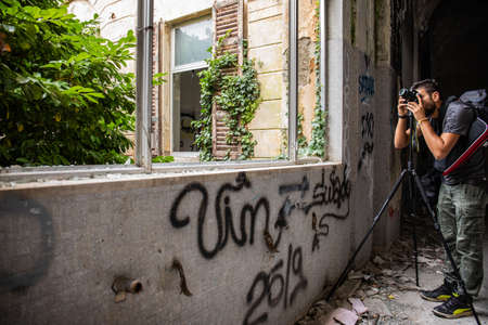 Young man take a photo in Abandoned psychiatric hospital - asylum - in Mombello, (Limbiate), Monza and Brianza, Lombardy, Italy