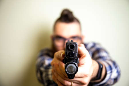 young man with plaid shirt holding a gun pointing at the camera