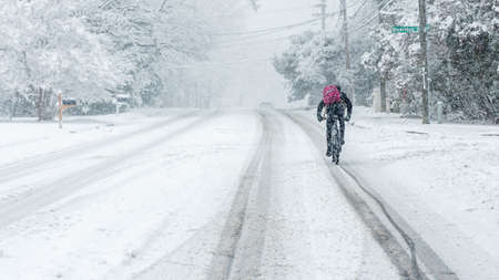 Man riding a bike in the snow on an intown street with purple backpack