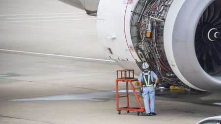 worker examining open engine compartment on jetliner