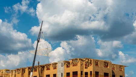 Construction workers on roof with crane and cumulus clouds in background Editorial