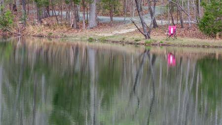 Reflection of pink fold up chair on lake with trees and buses Stock fotó