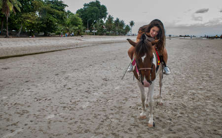 Young girl hugging a horse on the beach in Hua Hin Thailand
