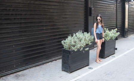Teen standing in front of store and planters painted black with sunglasses and shorts