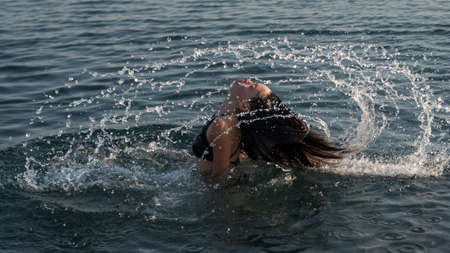 teen flipping hair in water and making a splash