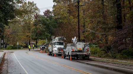 Carrboro, North Carolina, US-November 13, 2018: Workers repairing power lines after tree fell on them in storm 新闻类图片