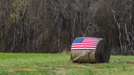 American flag on bale of hay with hand plow in front
