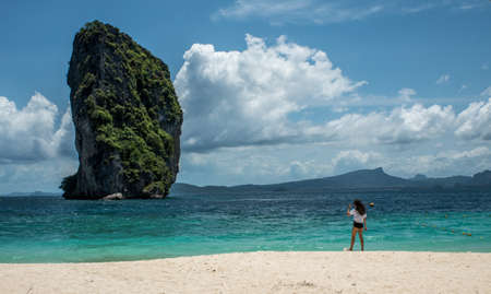 Teen girl standing on tropical beach in Thailand looking at island
