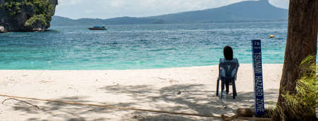 woman sitting on chair on beach in front of Sunami Hazard sign