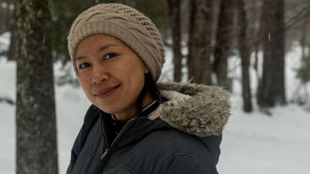 portrait of Asian woman with biege knit hat standing in snow Reklamní fotografie