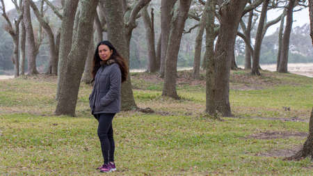 Asian woman with parka standing in front of trees in North Carolina State Park 免版税图像