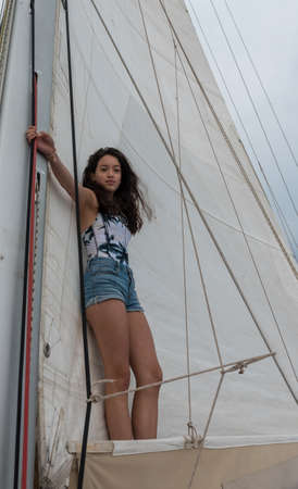young teen girl standing on the boom of a saillboat with sails behind her