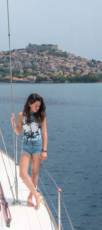 Young teen girl inshorts standing on deck of sailboat