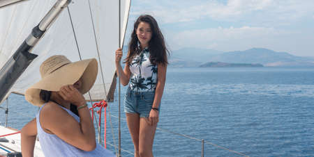 Mother with hat and daughter on sailboat with cloudy skies