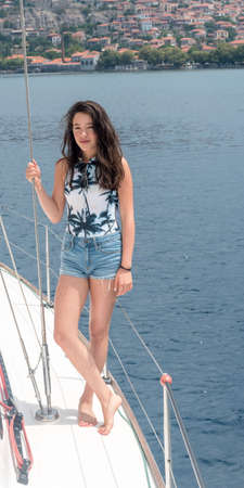 Young teen girl inshorts standing on deck of sailboat Stockfoto