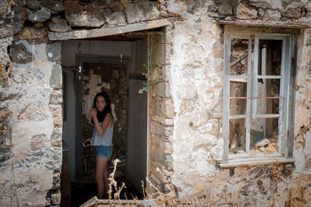 Woman standing in ruins of abandoned house in Greek Village Reklamní fotografie