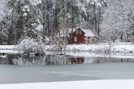 Red house in snow surrounded by woods behind a frozen pond
