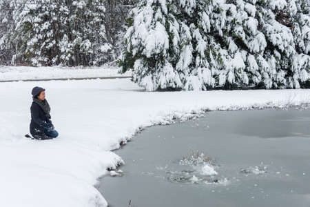 Asian woman with hat and winter coat kneeling in front of frozen pond after snow storm