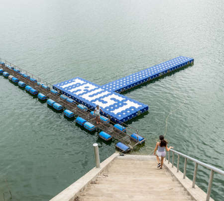 Teenager walking down stairs and mother standing on float at resevoir in Thailand 免版税图像