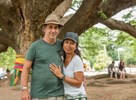 Husband and wife under the Thai Monkeypod Tree in Kanchanaburi Thailand 免版税图像
