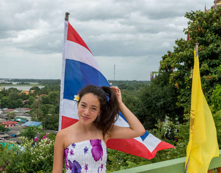 Smiling teen standing in front of Thai flag with town in the background
