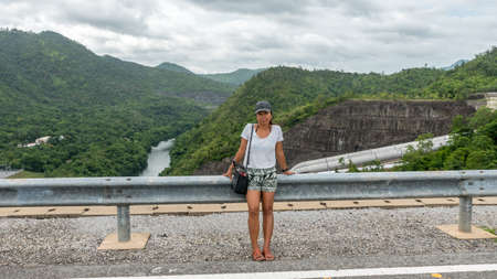 Asian woman sitting on guard rail in Thailand with river in the background