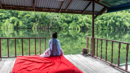 Woman sitting on red bed looking at river with reflection of trees in the water Imagens