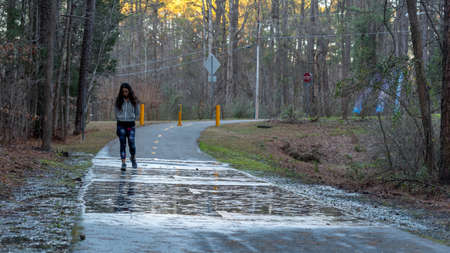 Woman walking on bikepath in forest after ran with reflections on the puddles