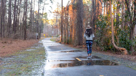 woman with hat  walking down empty bath in woods with puddles on bike path