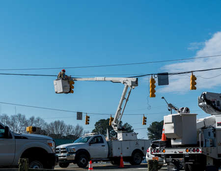 Power company worker in bucket above road repairing traffic light