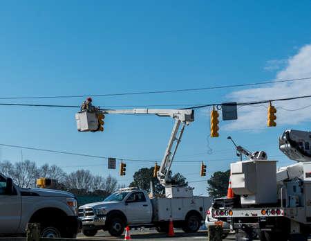 Trabajador de la compañía eléctrica en la cuchara por encima de la carretera reparación de semáforo