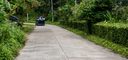 Students riding to school in small Thai village on pickup truck