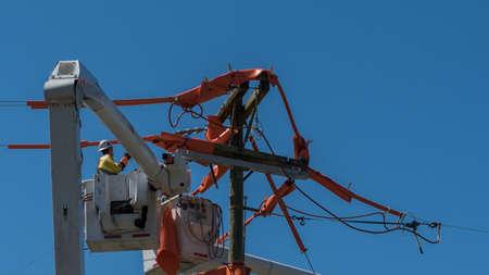 men in bucket on extended cherry pickers repairing electric wires Foto de archivo