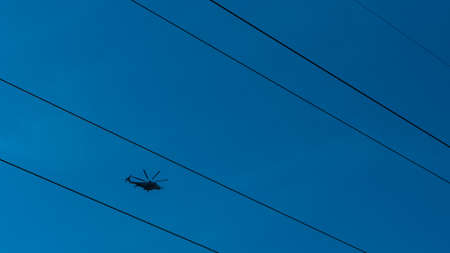 Helicopter flying between high tension wires with a clear dark blue sky Banque d'images - 121585764