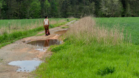 Back of woman in sarong walking away on dirt road with puddles in field