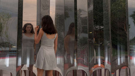Teen in grey dress standing in front of multiple mirrors with back to camera