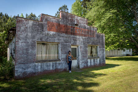 Asian woman in jeans and sneakers standing in front of dilapidated and abondoned restaurant  in Virginia 免版税图像