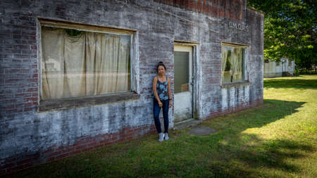 Asian woman in jeans and sneakers standing in front of dilapidated and abondoned restaurant  in Virginia Imagens
