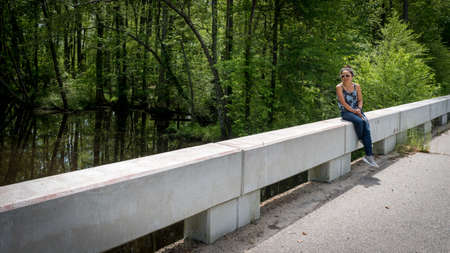 woman sitting on bridge near Swampy river off highway in Virginia with reflection in the water