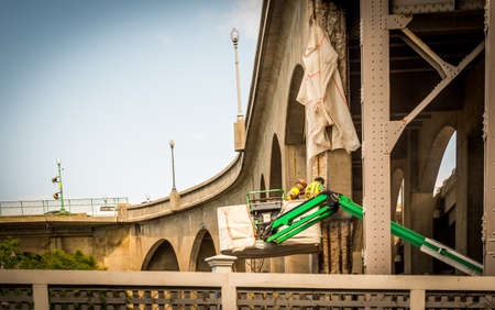 Two workers with hard hats in a bucket working on a bridge Stock fotó