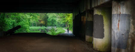 Woman walking under highway bridge along Chesapeake and Ohio Canal framed by the bridge Standard-Bild - 131362257