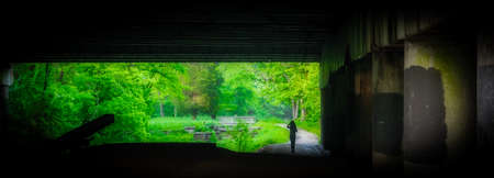 Woman walking under highway bridge along Chesapeake and Ohio Canal framed by the bridge 免版税图像