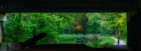 Woman walking under highway bridge along Chesapeake and Ohio Canal framed by the bridge Standard-Bild - 131363462
