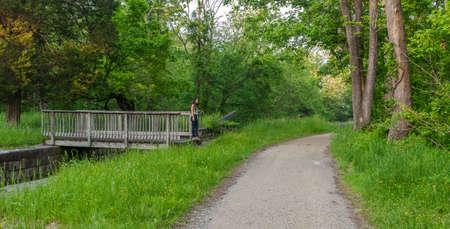 woman standing on bridge over lock on Chesapeake and Ohio Canal Standard-Bild - 131362592
